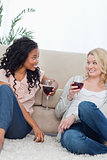 Two women sitting up against a couch are drinking wine