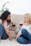 Two women are sitting on the ground leaning against a couch