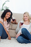 Two women smiling at the camera holding wine glasses