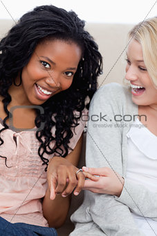 A woman  smiling at the camera is showing her friend her wedding