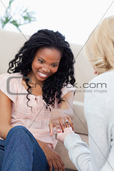A woman sitting down is showing her friend her wedding ring