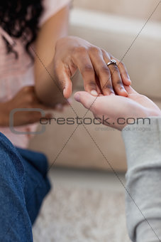 A hand with a wedding ring on it is placed in her friends hand