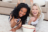 Two women lying on the ground with popcorn are smiling at the ca
