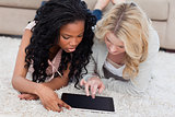 Two women are lying on the floor looking at a tablet