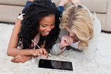 Two women are lying on the floor using a tablet