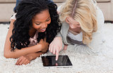 Two women lying on carpet are looking at a tablet