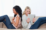 Two laughing women sitting back to back have a tablet computer