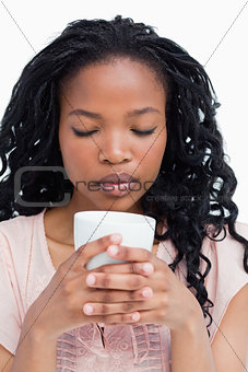A young woman with her eyes closed is smelling coffee out of a c