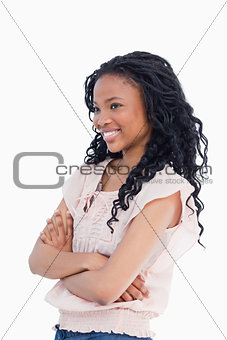 A smiling young woman with her arms folded looking away from the