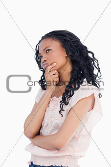 A young woman resting her head in her hand is thinking