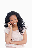 A smiling young woman is talking on her mobile phone