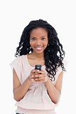 A beautiful woman looking at the camera is holding a mobile phon