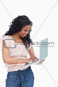 A happy young woman is typing on the laptop she is holding