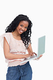 A young woman holding a laptop is smiling at the camera