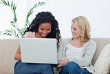 Two women with a laptop in front of them are laughing