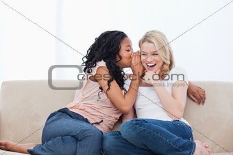 A woman is whispering into her smiling friends ear
