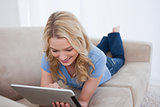 A smiling woman lying on a couch is using her tablet