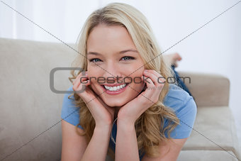 A smiling woman is resting her head on her hands