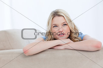 A woman resting her chin on her hands is thinking