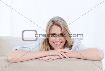 A smiling woman looking at the camera is resting her chin on her