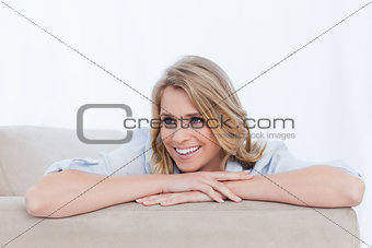 A woman with her arms resting is smiling