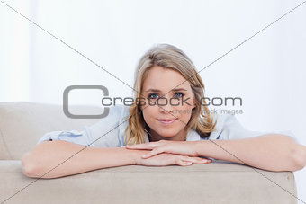 A woman with her arms resting is looking at the camera