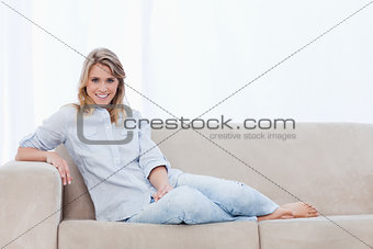 A woman smiling at the camera is sitting on a couch