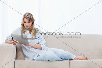 A woman sitting on a couch is using a tablet
