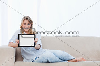 A smiling woman holding a tablet on in front of her