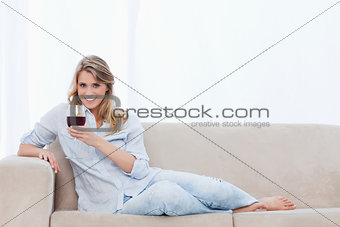 A smiling woman lying on a couch is holding a glass of wine