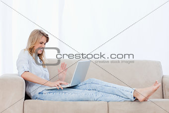 A happy woman sitting on a couch is using her laptop