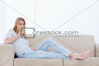 A woman lying on a couch is eating an apple