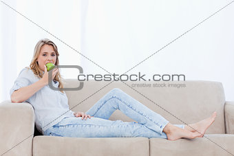 A woman eating an apple is lying on a couch