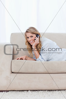 A smiling woman talking on her mobile phone is lying on a couch