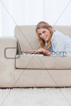 A woman lying on a couch is using a laptop