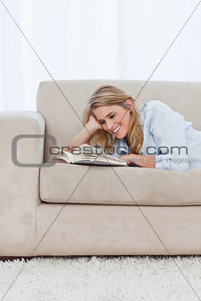 A smiling woman lying on a couch resting her head on her hand is