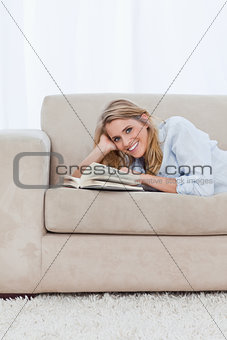 A woman looking at the camera is lying on a couch with a book