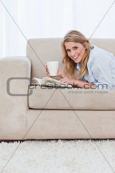 A woman with a book is looking at the camera and holding a cup o