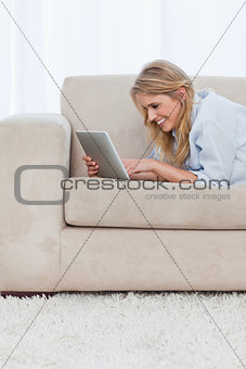 A smiling woman is lying on a couch using a tablet