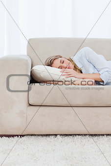 A woman is sleeping on a couch