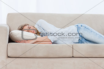 A sleeping woman is lying on a couch