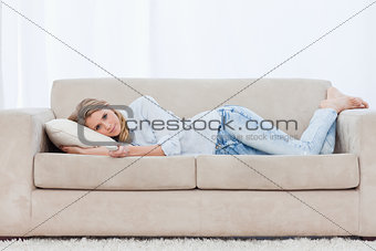 A woman holding a TV remote control is lying on a couch