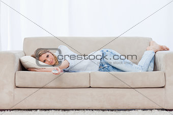 A woman lying on a couch resting is holding a television remote