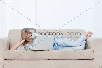 A woman lying on a couch resting her head on her hand is using h