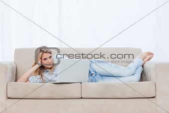 A woman looking at the camera is lying on a couch using her lapt