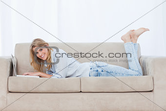 A smiling woman lying on a couch using a laptop