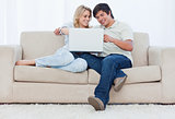 A smiling couple are sitting on a couch looking at a laptop