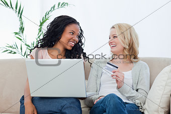 Two women looking at each other holding a bank card and a laptop