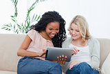 Two women sitting on a couch looking at a tablet computer