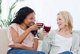 Two women holding wine glasses are smiling at each other